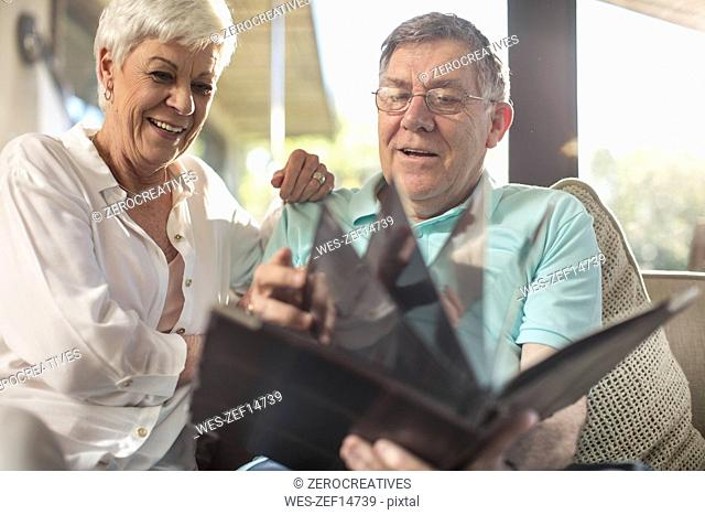 Happy senior couple sitting on couch looking at photo album