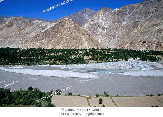 The Hunza river flows from the high plateau of the Hunza through the landscape of the Gilgit Valley. It is surrounded by spectacular mountain scenery
