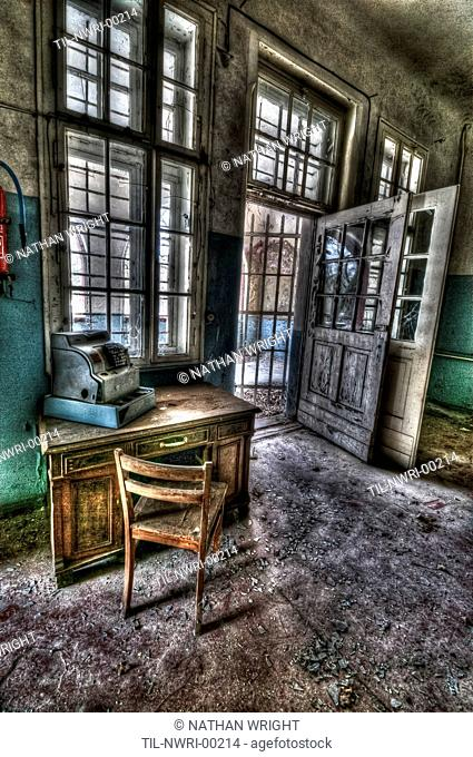 Abandoned lunatic asylum north of Berlin, Germany Cash till on desk with chair