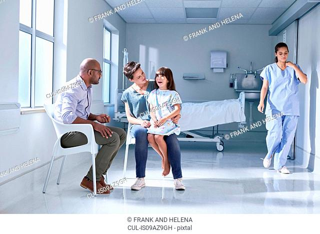 Male doctor talking to girl patient and her mother in hospital children's ward