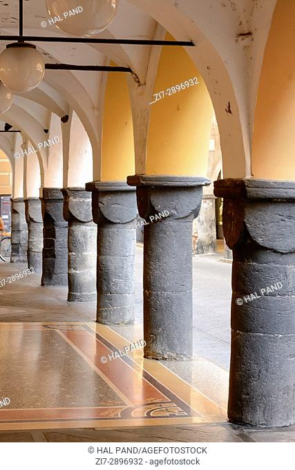foreshortening of stone columns of old medieval arched arcade, shot at Mediterranean little town of Chiavari, Genova, Liguria, Italy