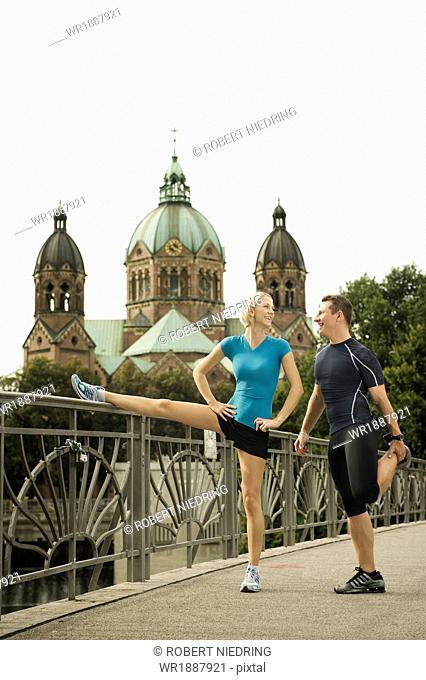 Young couple stretching on bridge, Munich, Bavaria, Germany