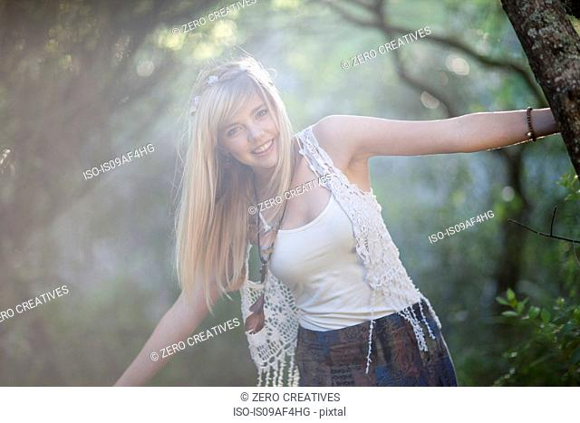 Portrait of teenage girl holding onto tree in woodland