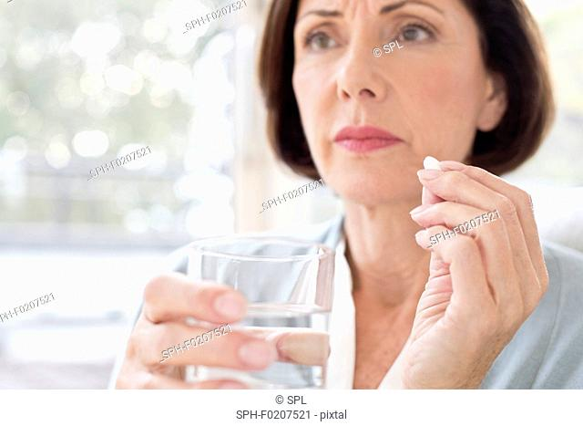 Mature woman taking tablet