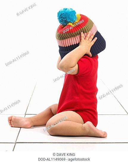 Baby boy (16 months) with colourful stripes woolly hat over head and face