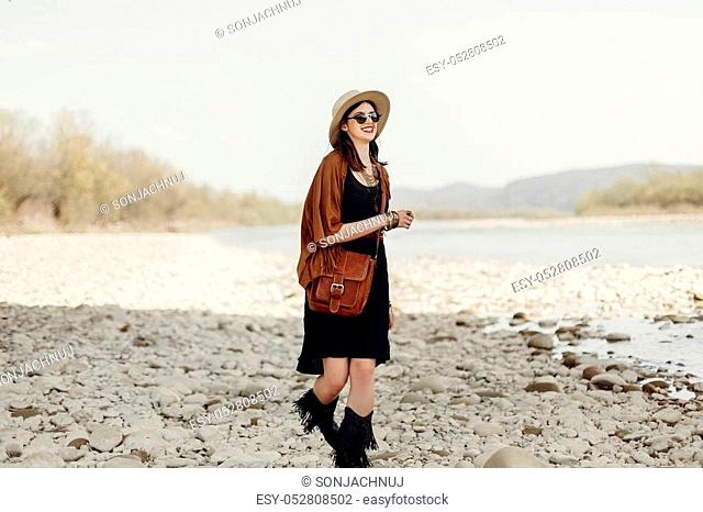 happy stylish hipster traveler woman in hat, fringe poncho walking near water river beach in mountains, gypsy boho girl. wanderlust summer travel