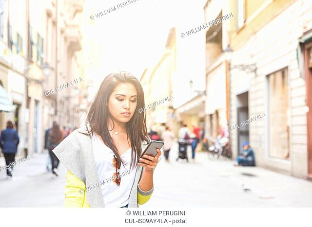 Woman in street texting on smartphone