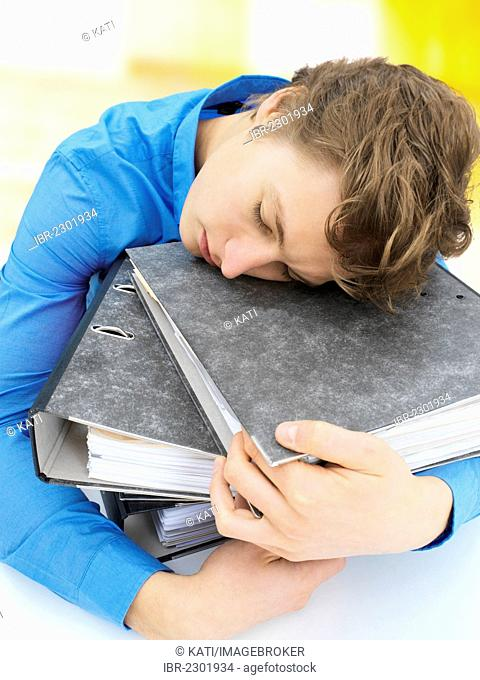 Young businessman sleeping on a stack of files