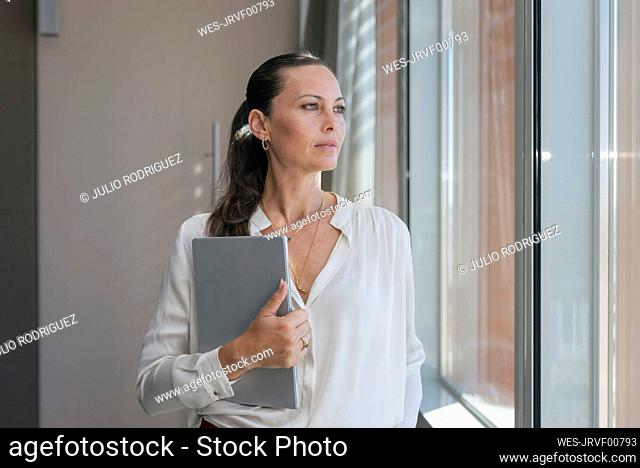 Female entrepreneur with digital tablet looking through window while standing in office