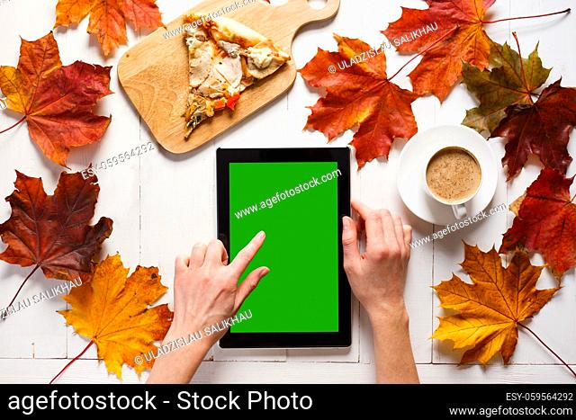 Autumn morning of contemporary young woman. Portable pc tablet, coffee and pizza on white timber table. Top view
