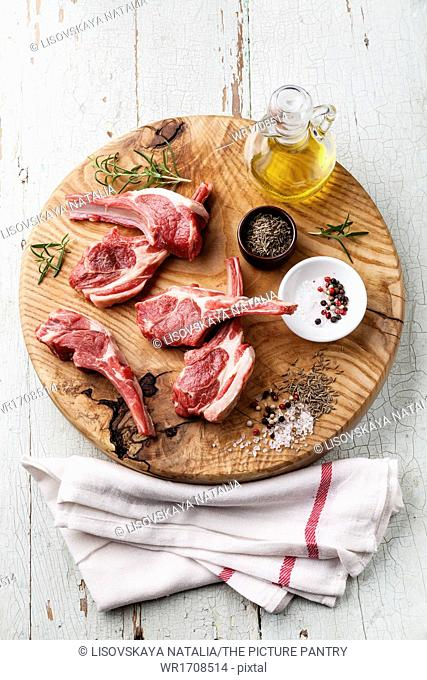 Raw fresh lamb ribs with salt, pepper and cumin on wooden cutting board on blue background