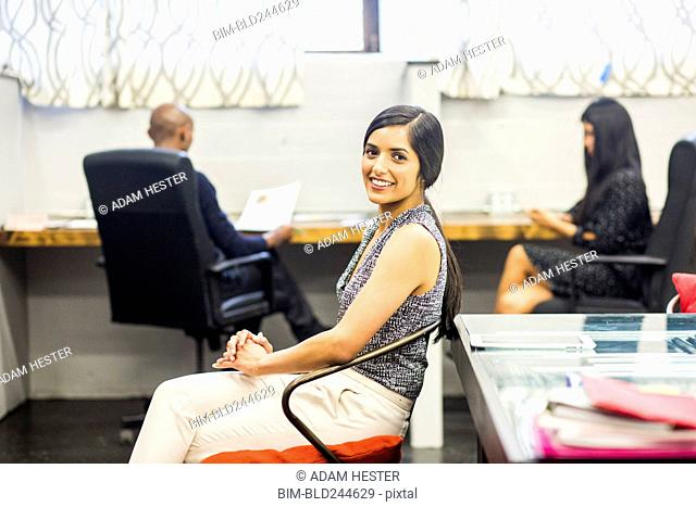 Portrait of smiling Asian woman sitting in office