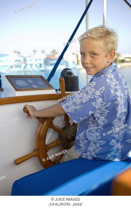 Boy sitting at helm of boat