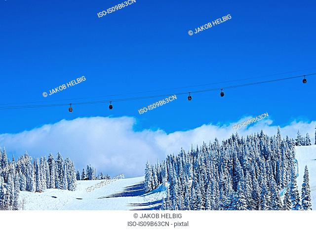 Cable car over snow covered mountains and blue sky, Aspen, Colorado, USA