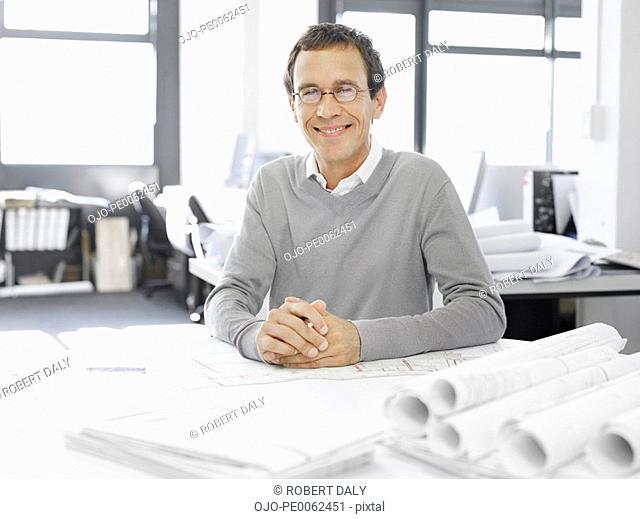 Architect posing with blueprints