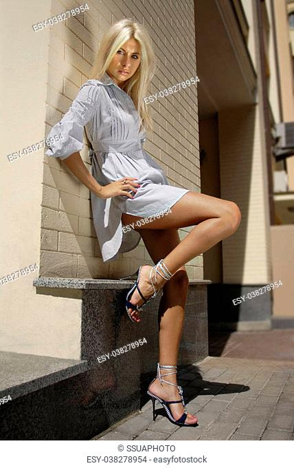 blonde beautiful woman stands near wall of building