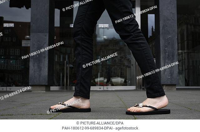 ILLUSTRATION - 12 June 2018, Germany, Bremen: A woman wearing flip-flops walking past the entrance to the Bremen Buergerschaft legislative assembly.