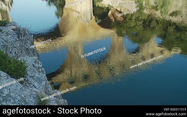 Pont du Garde, France : reflection of the Nimes Roman aqueduct crossing the Gardon River in early morning sun