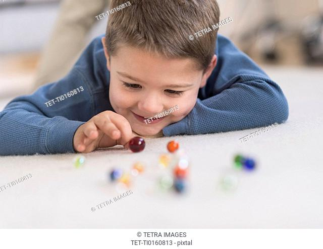 Boy (4-5) playing with marbles