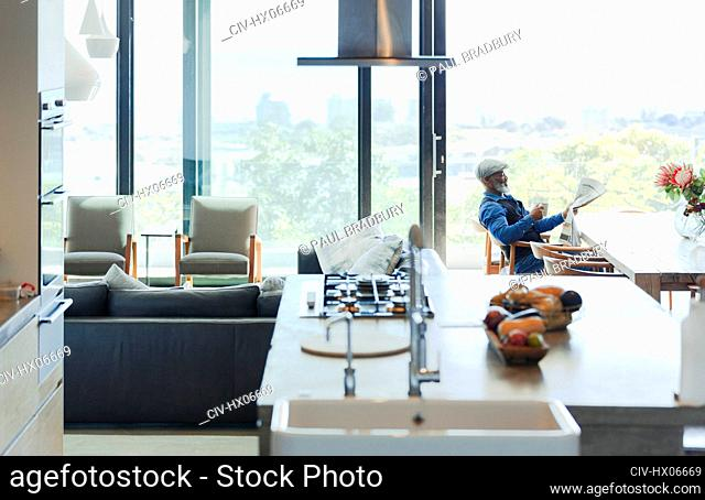 Man reading newspaper in modern, open plan home