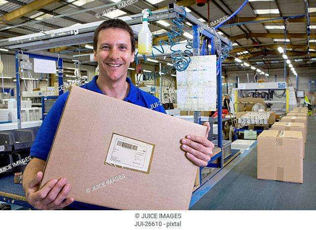 Worker in warehouse on assembly line holding cardboard box