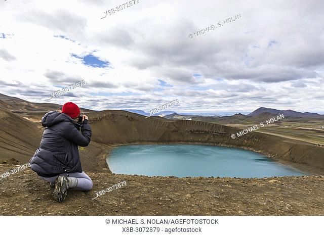 Photographer at the 300 meter deep crater called Víti off the north coast of Iceland