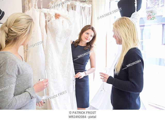 Sales clerk in bridal shop showing wedding dress to customers