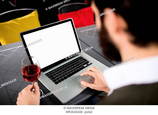 Man using laptop while having glass of wine