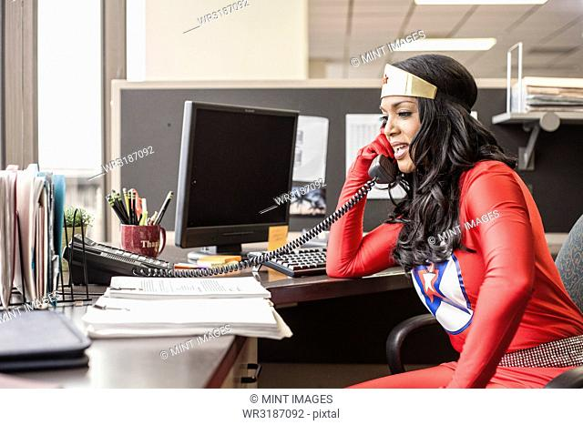 A black office superhero businesswoman takes a call in her office from a client