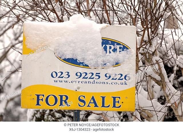 house for sale board partially obscured by snow