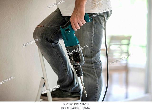 Builder holding drill on ladder