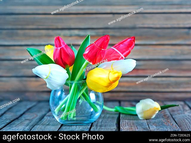 tulips in vase and on a table