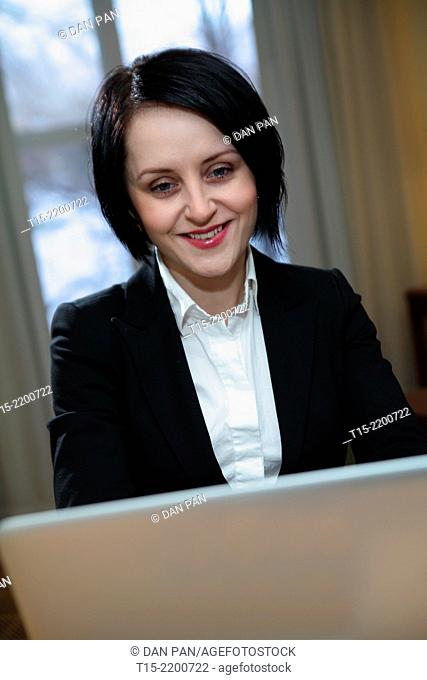 A black haired young woman working on a computer