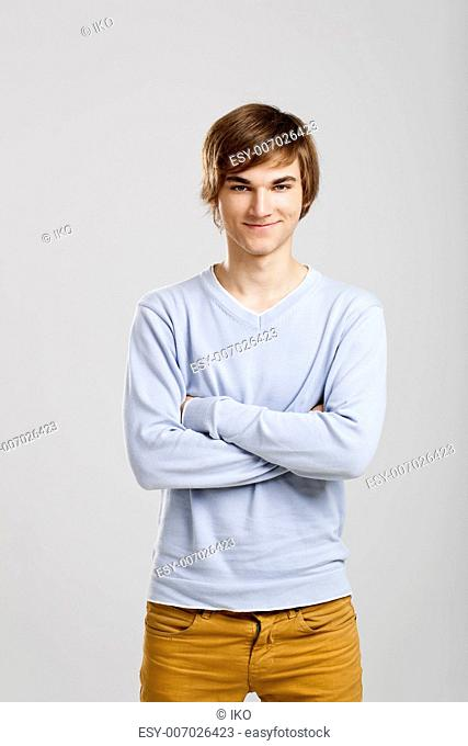 Portrait of a handsome young man standing over a gray background