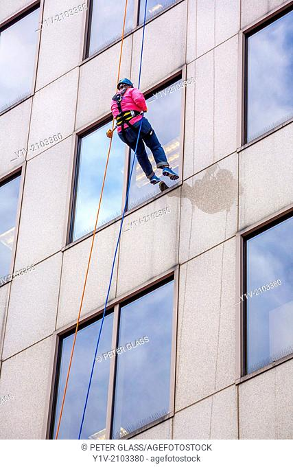 Woman repelling down the side of an office building