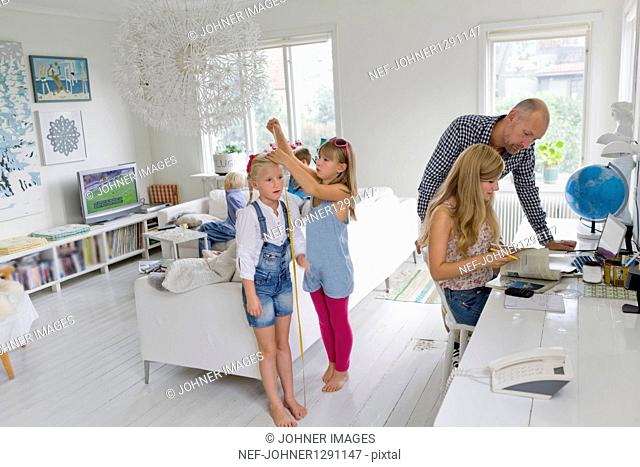Father assisting teenage daughter doing homework, two other girls playing in background