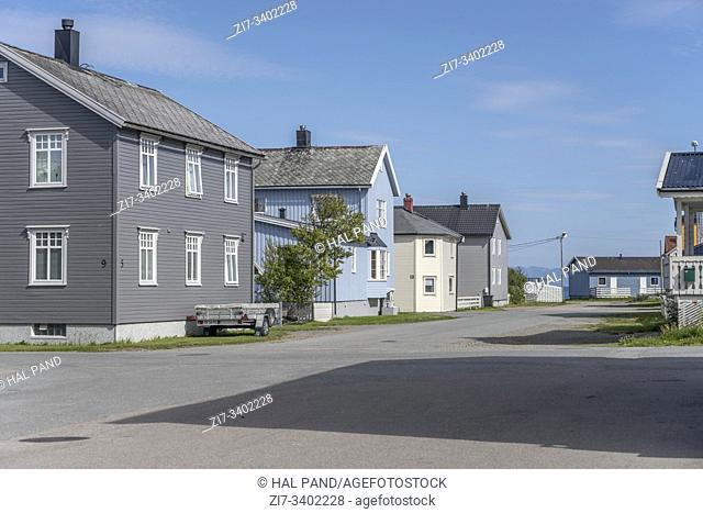 cityscape with cart parked in street to sea side flanked by spaced-out traditional houses at artic touristic village, shot under bright summer light at Andenes