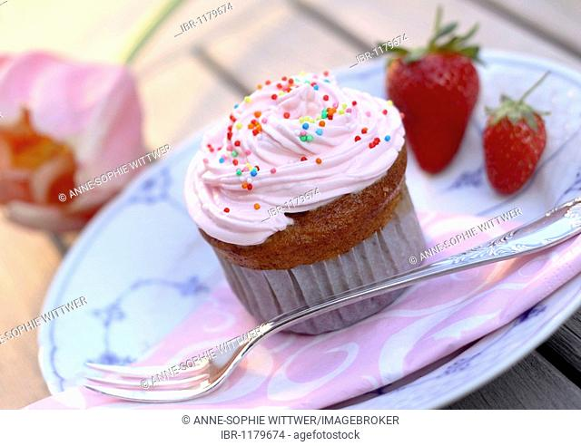 Cupcake muffin with cream, strawberries and pearl sugar on plate