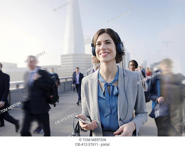 Smiling, confident businesswoman listening to music with smart phone and headphones on urban pedestrian bridge