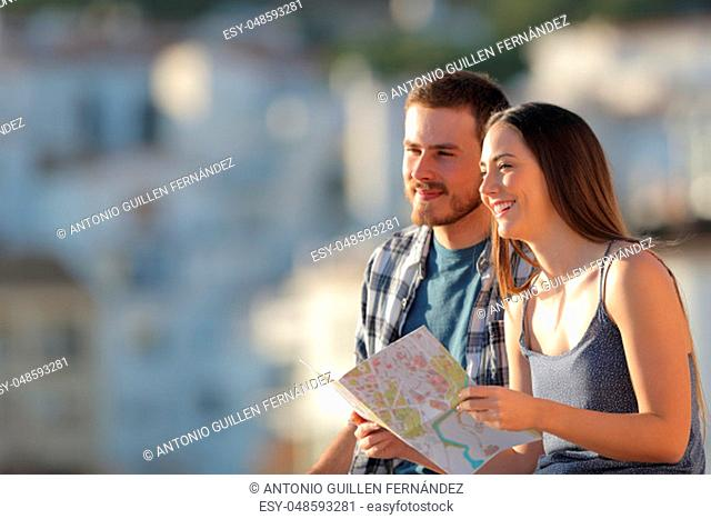 Happy couple of tourists holding paper map contemplating views in a town on vacation