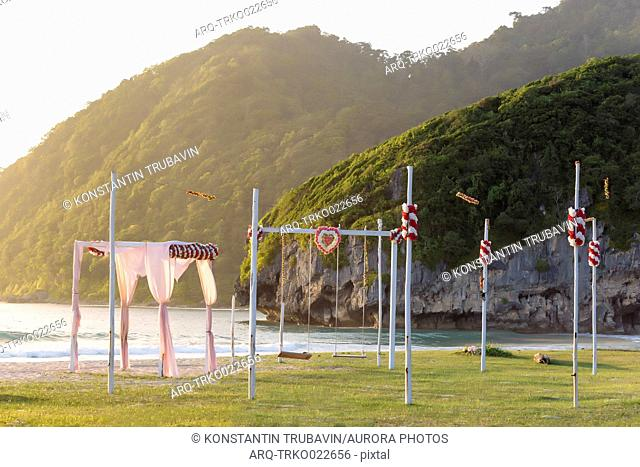 View of tent and swings on seashore with mountains in background, Banda Aceh, Sumatra, Indonesia