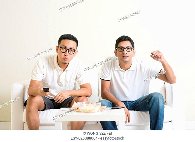 Men sitting on couch watching football match on television, Asian people friendship at home
