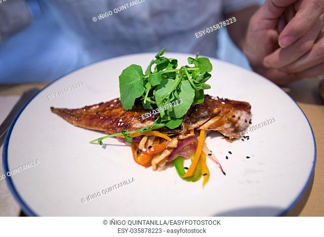 grilled fish loin with vegetables, carrot, onion, green and red pepper and mushrooms, and raw green rucula on white plate in restaurant