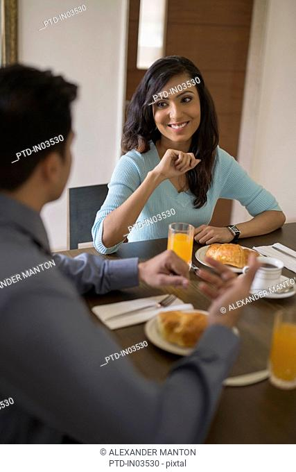 India, Woman smiling at man at breakfast table