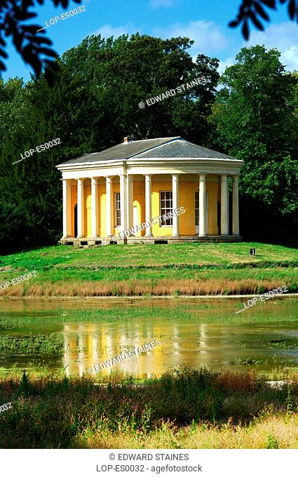 England, Buckinghamshire, West Wycombe, The Temple Of Music in West Wycombe Park with lake in foreground. West Wycombe village is owned by the National Trust
