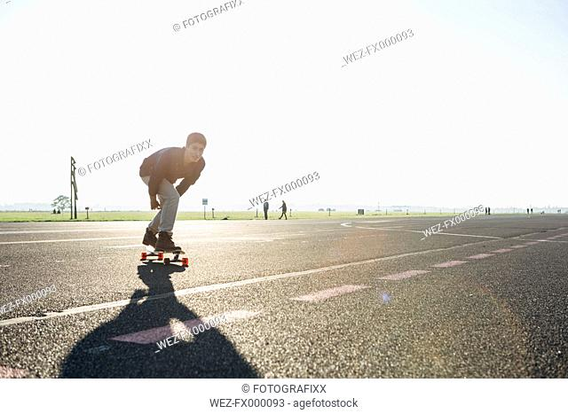 Germany, Berlin, Tempelhof Field, young man skating with longboards
