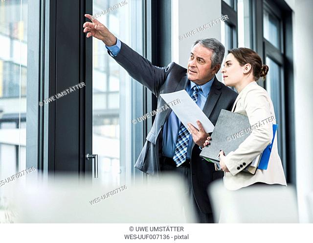 Senior businessman and young businesswoman talking at the window