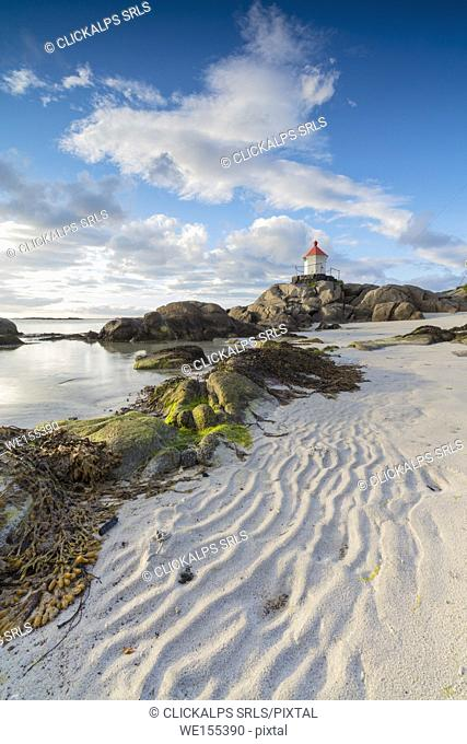 Midnight sun lights up lighthouse on cliffs surrounded by sea and sand Eggum Unstad Vestvagøy Lofoten Islands Norway Europe