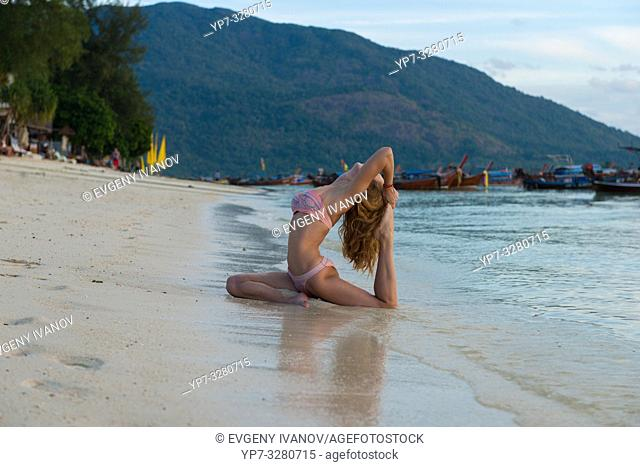 Girl practicing yoga in pigeon pose on the beach with Thai longtail boats, Ko Lipe island