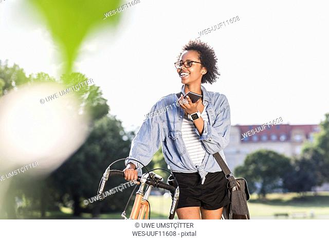 Smiling young woman with cell phone and bicycle in park
